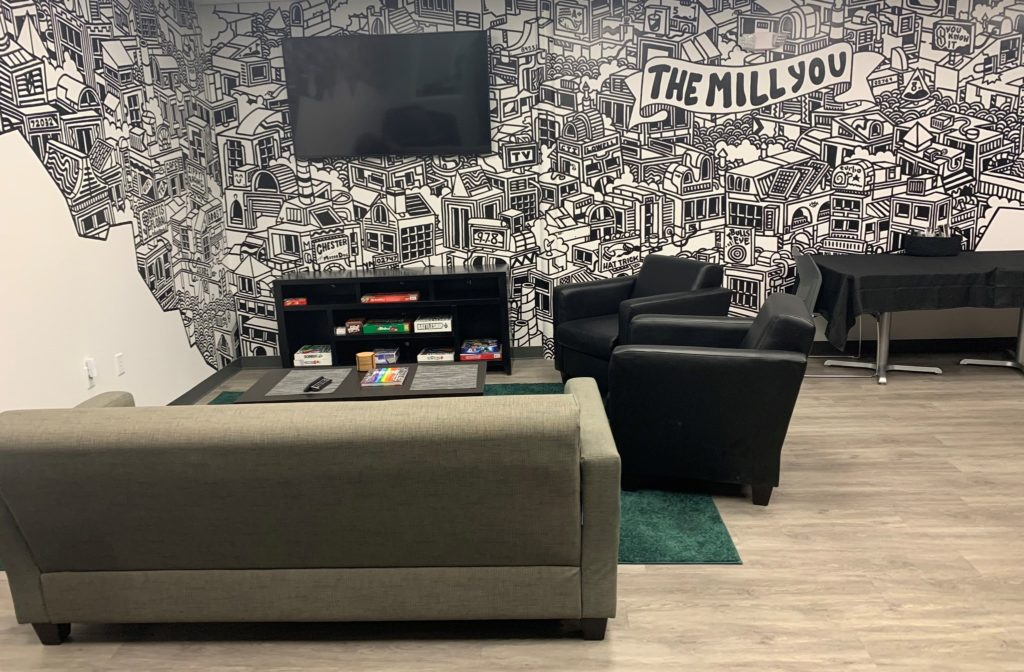 Social area in Community Teamwork, Inc's  Mill You with a couch, chairs, TV, bookcase, and a black and white wall mural.