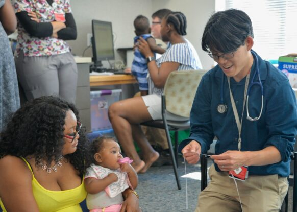 A doctor speaks with a woman and her daughter in Codman Square Health Center as part of the TEAM UP for Children initiative.
