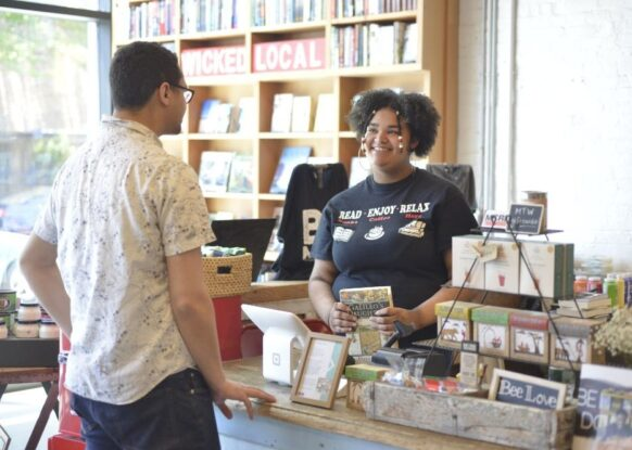 A young woman helps a client checkout at More Than Words' recently expanded bookstore.