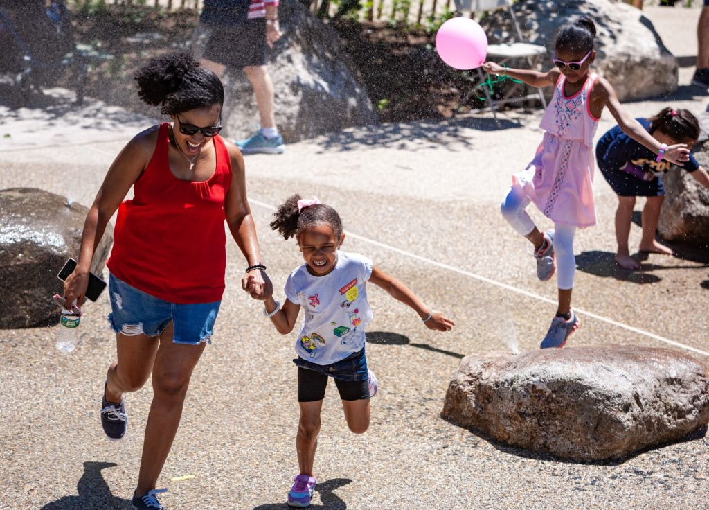 A laughing woman and young girl run through a water feature on the opening day of Martin's Park at the Smith Family Waterfront.