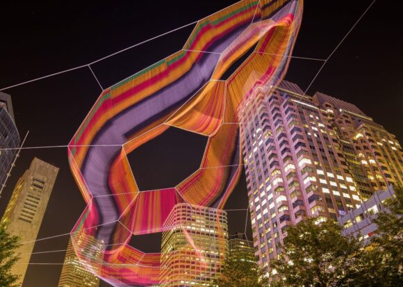 Janet Echelman's aerial sculpture over the Rose Kennedy Greenway from below at night.