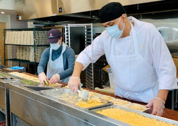 A man and a woman wearing protective face masks, aprons, and gloves package emergency meals at Community Servings.