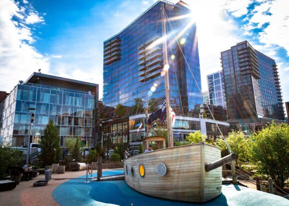 A play ship in Martins Park at the Smith Family Waterfront with tall buildings and glistening sun in the background.