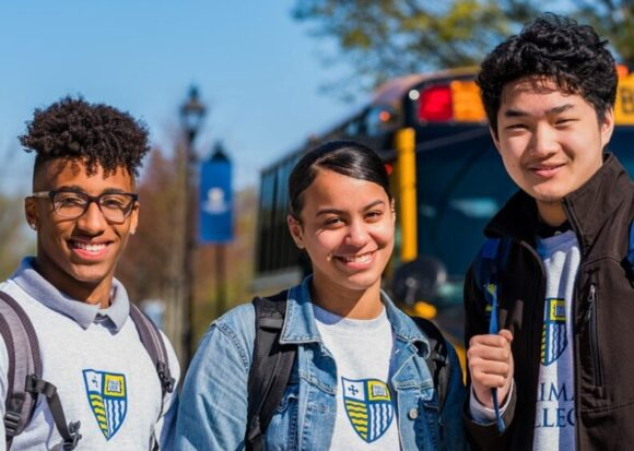 Three Early College students outside at Merrimack College with a school bus in the background.